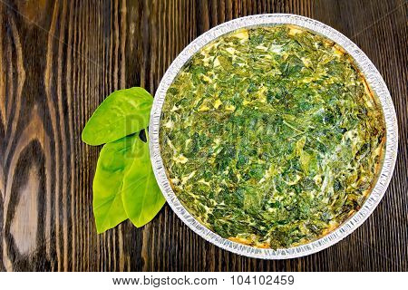 Pie celtic with spinach in form of foil on board