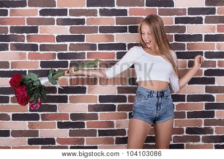Young Beautiful Blond Girl Throws Roses Out