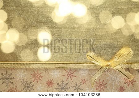 Golden ribbon bow on paper textured background