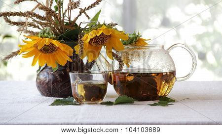 Tea In A Transparent Teapot And Sunflowers In A Ceramic Vase