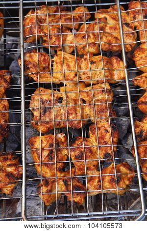 fresh raw chicken in meat holder on grid grill over burned charcoal spiced with salt pepper paprika ready to serv party
