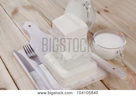 healthy dairy food fresh white greek goat sheep feta cheese on plate with milk in glass and full jug cherry tomatoes french bun over light wooden table with cutlery