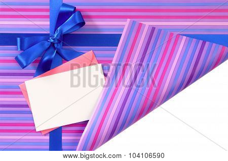 Blue Gift Ribbon Bow On Candy Stripe Wrapping Paper, Corner Folded Open Revealing White Copy Space,