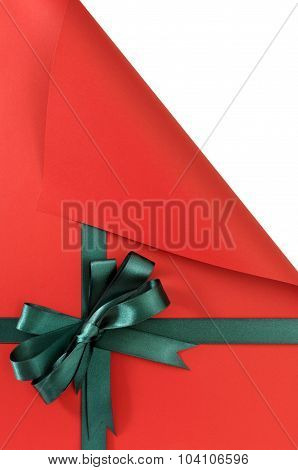 Green Gift Ribbon Bow On Plain Red Background Paper, Top Corner Curled Open Showing White Copy Space