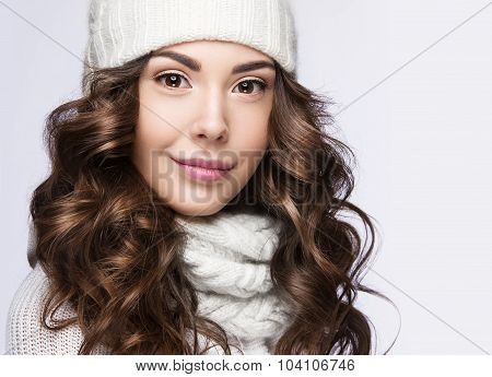 Beautiful girl with gentle makeup, curls and smile in white knit hat. Warm winter image. Beauty face