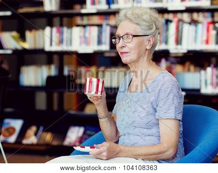 Elderly lady in the libary with cup of tea