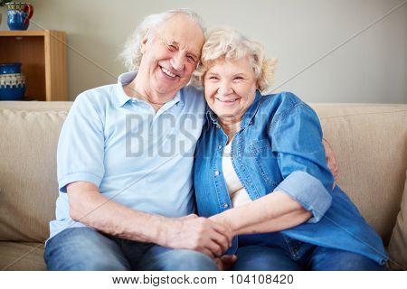 Happy senior man and woman sitting on sofa