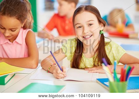Happy schoolgirl looking at camera at drawing lesson