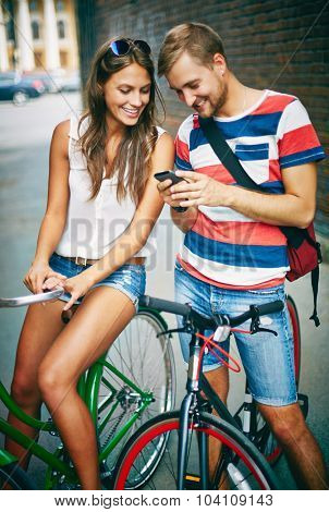 Young couple on bicycles using cellphone outdoors