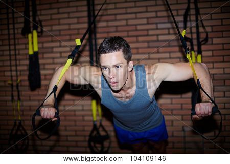 Young man in activewear strengthening arm muscles on special facilities