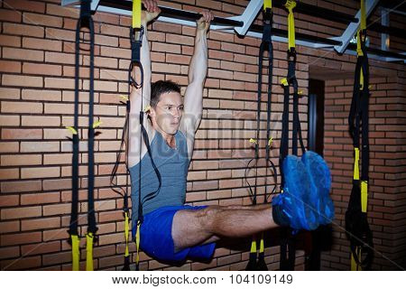 Young athlete doing exercises on special equipment in sportsclub
