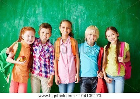 Happy kids with backpacks standing in row along school blackboard