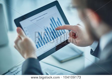 Businessman pointing at chart and graph in digital tablet