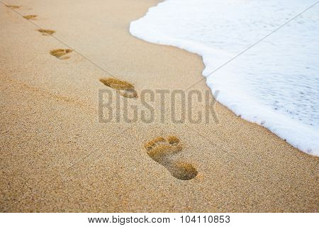 Footprints In The Sand And Sea Wave