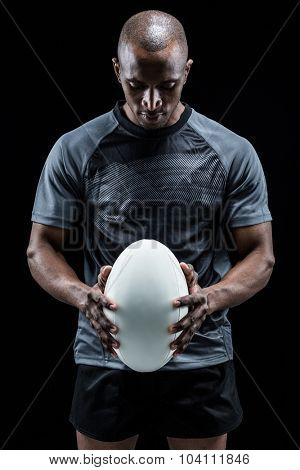 Thoughtful athlete looking at rugby ball standing against black background