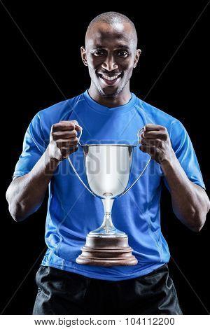 Portrait of happy sportsman holding trophy over black background