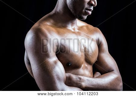 Mid section of shirtless athlete with arms crossed against black background