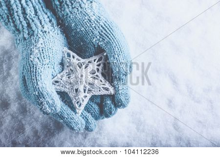 Female hands in light teal knitted mittens with entwined white star on a white snow background. Winter and Christmas cozy concept.