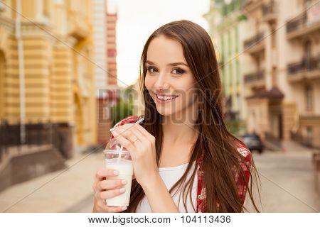 Good-looking Girl Drinking A Milkshake On The Street