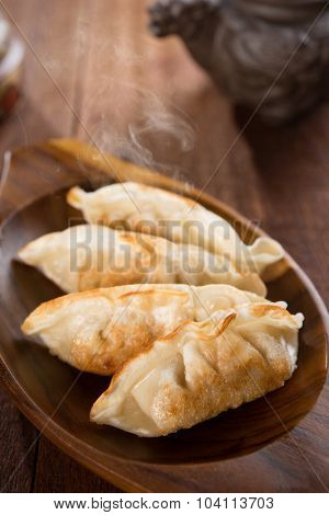 Fresh pan fried dumplings on plate with hot steams. Asian food on rustic old vintage wooden background.