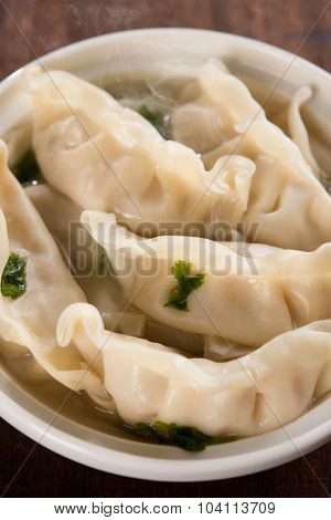 Close up fresh dumplings soup on plate with hot steams. Chinese food on old vintage wooden background.