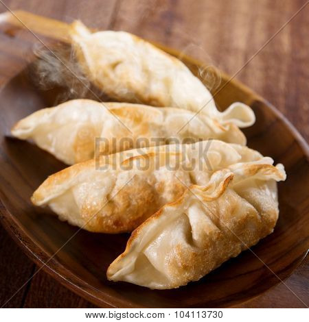 Fresh pan fried dumplings on plate with hot steams. Asian dish on rustic old vintage wooden background.