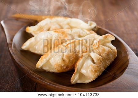 Fresh pan fried dumplings on plate with hot steams. Asian meal on rustic old vintage wooden background.
