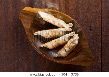 Top view fresh pan fried dumplings on plate with hot steams. Asian food on old rustic vintage wooden background.