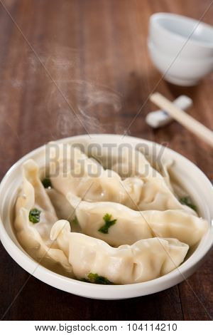 Fresh dumplings soup on plate with hot steams. Chinese meal on old vintage wooden background.