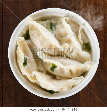 Top view fresh dumplings soup on plate with hot steams. Chinese food on rustic old vintage wooden background.