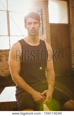 Muscular man sitting on plyo box at the ground