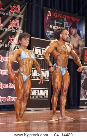 Bodybuilding Duo In Relaxed Front Pose On Stage