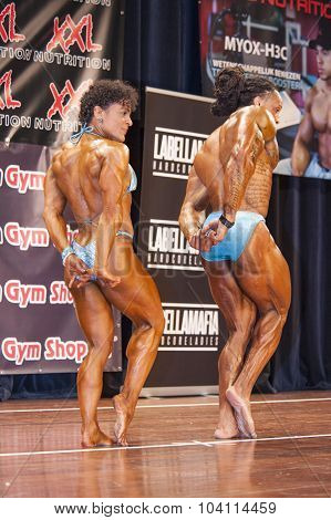 Bodybuilding Duo In Triceps Pose On Stage