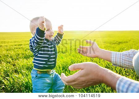 Father giving a hand to baby boy who making his first steps