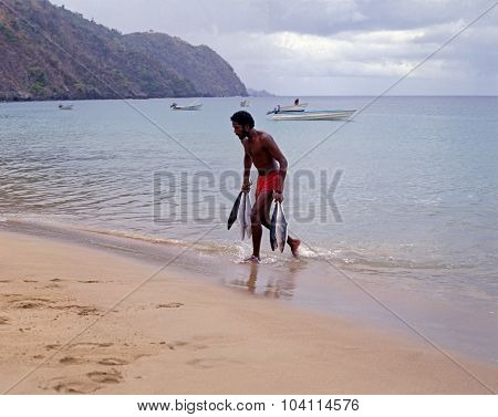 Fisherman carrying fish from sea.
