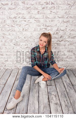 Good-looking Girl With Tablet And Cup Sitting On The Floar
