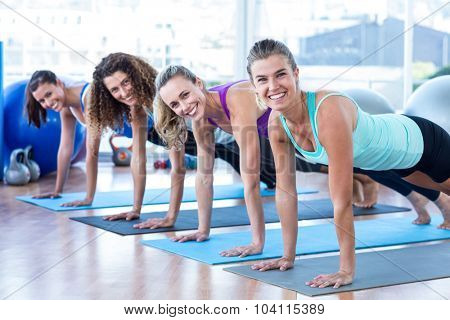 Portriat of cheerful women doing plank pose on exercise mat in fitness studio