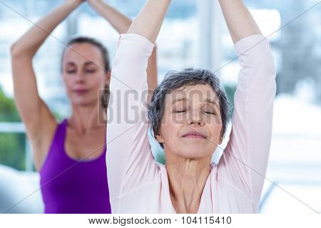 Women meditating with joined hands and eyes closed in fitness studio