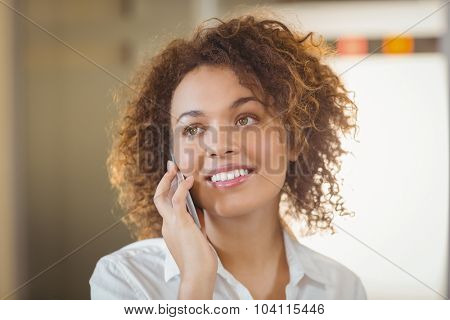 Smiling businesswoman on call in office
