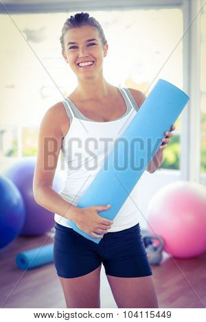 Portrait of woman smiling while holding yoga mat in fitness studio