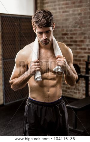 Muscular man holding towel at the gym