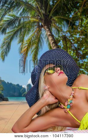 Young woman relaxing on the beach at exotic resort