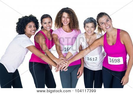 Portrait of smiling athletes putting their hands together while standing against white background