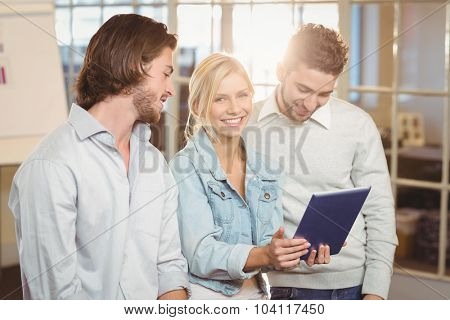 Portrait of smiling businesswoman holding laptop standing with male colleagues in creative office