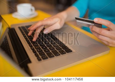 Cropped hand of woman using laptop while holding credit card in cafe