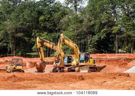 Three Yellow Construction Machines