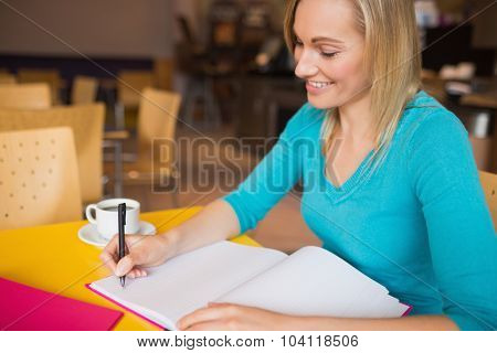 Young woman smiling while writing on book at table in restaurant