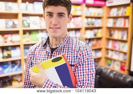 Portrait of confident young man with book standing against bookshelf in library