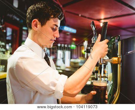 Barkeeper holding beer glass below dispenser tap at bar counter