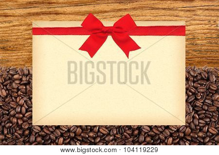 Postcard With Red Bow On Roasted Coffee Beans And Wooden Background